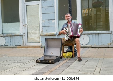 Ruse city, Bulgaria - July 12 2018. Street performer sing to accordion on the Alexandrovska pedestrian street in Ruse city, Bulgaria