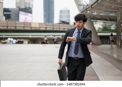 Rush Asian Chinese businessman running and looking at watch to check time on city walk. Young man late for train transportation, work, meeting. Office life and business competition.
