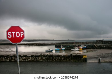 "RUSH ,DUBLIN COUNTY, IRELANDâ?? October 08, 2017 :The road sigh ""stop"" against the background of the harbor on a cloudy day."