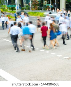 Rush hour, business people walking at crosswalk in downtown, motion blur, Singapore