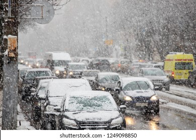 rush hour, city during heavy snowfall, snowstorm shackled streets, highways, hindering traffic, a lot of cars slowly go about their business, reduced visibility, danger of accidents, careful driving