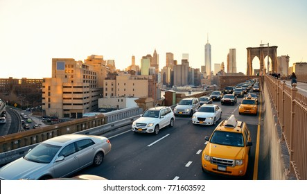 Rush hour traffic in downtown Manhattan at sunset with Brooklyn Bridge in New York City