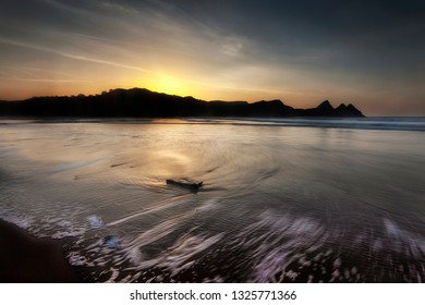 Rushing outgoing tide at Three Cliffs Bay and driftwood on the Gower peninsula, Swansea, South Wales, UK