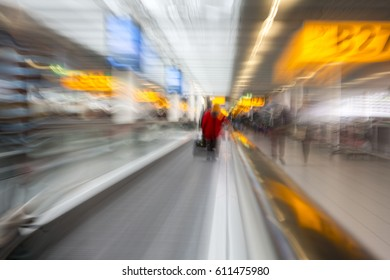 Rushing through the airport terminal to catch the next layover flight. Motion blurry image on an escalator. Last minute hurry to not to be late to the gate and miss the flight.