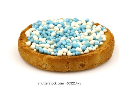 a rusk with blue and white anise seed sprinkles served in Holland when a baby boy is born on a white background