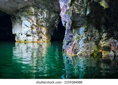 Ruskeala, Republic of Karelia (Kareliya), Northwest Russia. Beautiful underground lake with brigh emerald green water and stone columns with moss in natural day light in old abandoned marble quarry