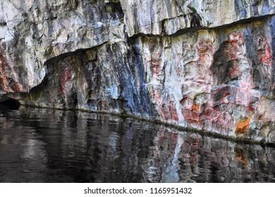 Ruskeala, Republic of Karelia (Kareliya), Northwest Russia. Beautiful natural stone wall reflected in lake water in old abandoned marble quarry