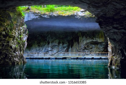Ruskeala, Republic of Karelia (Kareliya), Russia. Beautiful underground lake with smoke over the water and cave walls in natural day light coming from outside in old abandoned marble quarry