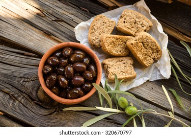 Rusks and black olives on rustic wooden table.