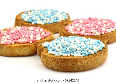 rusks with white and blue and white and pink anise seed sprinkles served in Holland when a baby boy or girl is born on a white background