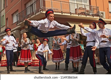 Russi, Ravenna, Italy - August 2, 2018: The folk dance ensemble Rejoice the Russians from Azov, Russia, performs traditional Cossack dance in the city street during the International Folklore Festival