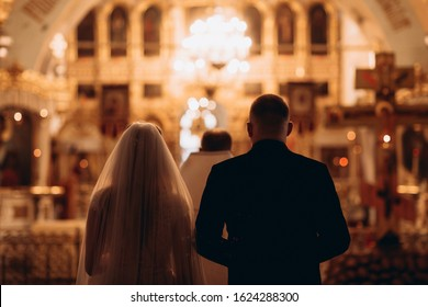 Russia, 2020 Orthodox church, sacrament of a wedding ceremony, couple, priest, golden church interior, candles, icons, altar, prayer