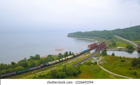 Russia, Baikal - August 02, 2018: Trans-Siberian Railway, the coast of Lake Baikal. Movement of trains on the iron bridge across the river flowing into Baikal, From Drone