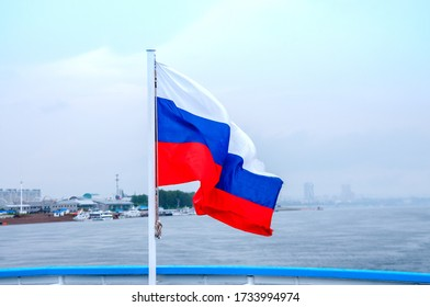 Russia, Blagoveshchensk, July 2019: Tricolor flag of Russia on the background of the Amur river near the city of Blagoveshchensk