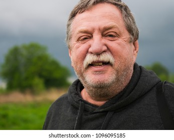 Russia. Cheerful and happy elderly mustachioed man portrait in nature