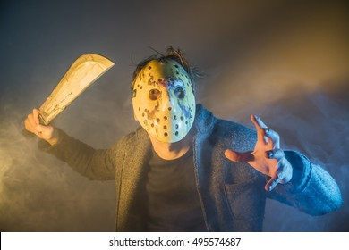 Russia, Chelyabinsk - August 13, 2016: Cosplayer costume one caucasian man serial killer with mask portrait in silhouette studio, Scary hockey white mask on young man  with machete