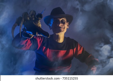 Russia, Chelyabinsk - August 13, 2016: Cosplayer costume one man Freddy Krueger is a serial killer with a glove c sharp knives in the mist, background for Halloween, A Nightmare On Elm Street