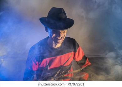 Russia, Chelyabinsk - August 13, 2016: Cosplayer costume one man Freddy Krueger is a serial killer with a glove in the mist, background for Halloween