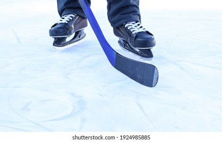 Russia, Chelyabinsk, February 25, 2021: A man in skates on ice with a hockey stick. View only feet.