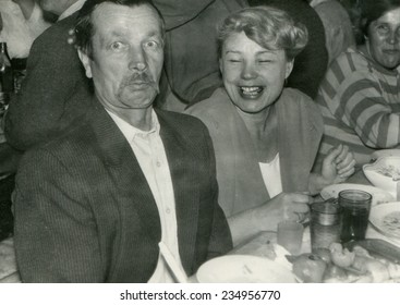 RUSSIA - CIRCA 1950s: An antique photo shows portrait of a Mature man and woman at the banquet table.