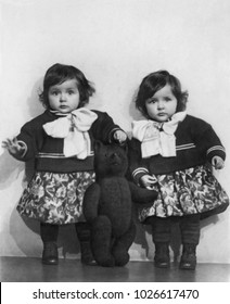 RUSSIA - CIRCA 1954s: Vintage photoof Portrait of girls nice twins with teddy bear in a photography studio. Retro black & white photography.