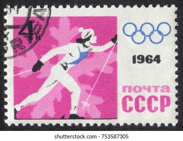 """RUSSIA - CIRCA 1964: A stamp printed in USSR (Soviet Union), shows a """"cross-country skiing"""" woman and Russian Olympic Emblem. Devoted to IX Olympic Winter Games at Austria, circa 1964"""