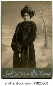 RUSSIA - CIRCA  the end of 19 - early 20 century: An antique photo shows woman in fur coat and hat with clutch in their hands, Kherson, Russian Empire Russian text: Leonid Koff (photographer), Kherson