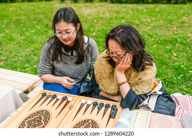 Russia, city Moscow - September 6, 2014: Young girls play a backgammon