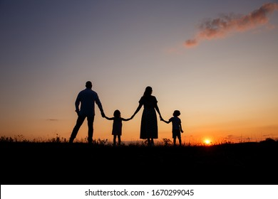 Russia, the city of Stavropol August 6, 2019. family on the background of the sunset stands holding hands silhouettes on the background of the sunset