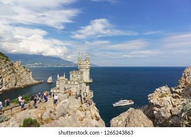 Russia, Crimea, Yalta, Gaspra-September 10, 2018: Tourists visiting the old Gothic castle swallow's Nest on the southern coast of Crimea. Over the blue sea beautiful cloudy sky