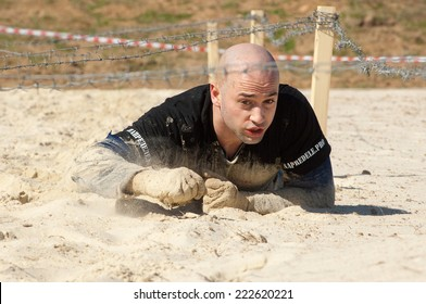 RUSSIA, DMITROV REGION, SHUKOLOVO VILLAGE - APRIL 26: Unidentified man crawling on sandy place on survival festival game NaPredele (On the edge) on April 26, 2014, Shukolovo village, Russia