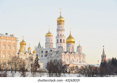 Russia. Ensemble of Moscow Kremlin. View on Kremlin cathedrals and Ivan the Great bell tower from Bolshoi Moskvoretsky bridge at a winter sunrise. Close up view