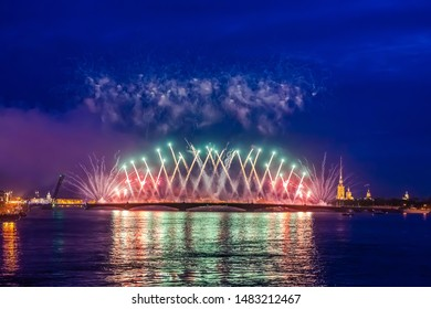 Russia. Fireworks over the Neva. St. Petersburg on a festive evening. Salute in the evening sky. Stay in the city. The fireworks on the background of the Trinity bridge. Salute reflected in the water.