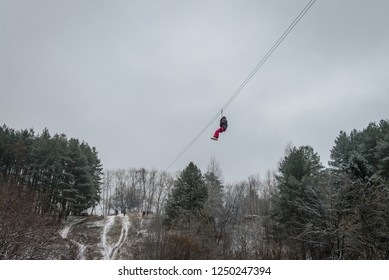 Russia, Izhevsk - November 18, 2018: Zipline. Woman gliding on rope trolley over ravine on high altitude. Extreme and active leisure.