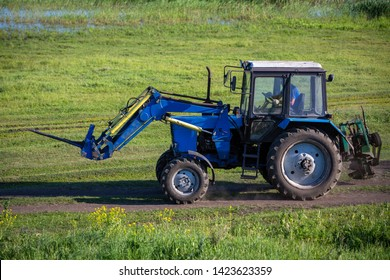 Russia, June 2019, Kaluga region. A tractor is driving along a road in a meadow. Summer sunny day. Blooming colza. Russian province.