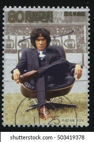 RUSSIA KALININGRAD, 18 MARCH 2016: stamp printed by Japan, shows an asian man sitting in the chair on tribune background, circa 2006