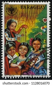 RUSSIA KALININGRAD, 19 APRIL 2017: stamp printed by Paraguay, shows children singing by Christmas Tree, circa 1982