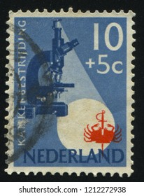 RUSSIA KALININGRAD, 21 JUNE 2017: stamp printed by Netherlands shows Microscope and Crab, circa 1955