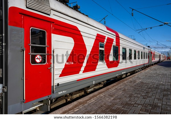 Russia, Karelia, Petrozavodsk: Train of Russian state-owned Russian Railways (OAO Rossiyskie zheleznye dorogi - OAO RZhD) with red white brand and platform at Central Train Station. Jul 10, 2019