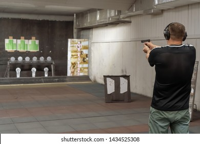 Russia, Kazan - June 23, 2019:  Man in shooting range in shooting action with GLOCK 19, view from behind o holding a pistol taking aim away from the camera with shallow depth of field.