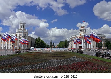 Russia, Kemerovo -10.06.2019. Flower bed in the city center, the post office building, the city hall against the blue sky with clouds
