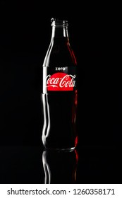 Russia Kemerovo 13-12-2018 Closeup bottle of Coca Cola on black background with beautiful flare reflected from the glass. Concept of dependence on sweets and carbonated drinks, diet, weight loss
