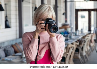 Russia Kemerovo 2019-03-10 girl photographer taking pictures on professional camera Canon 5D Mark IV in restaurant. Concept banquet, photoshoot new menu, lifestyle, freelancer, profession, designer
