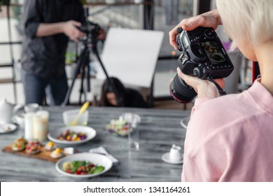 Russia Kemerovo 2019-03-10 girl photographer taking pictures on professional camera Canon 5D Mark IV and various dishes, salads on table in restaurant. Concept banquet, photoshoot new menu, lifestyle