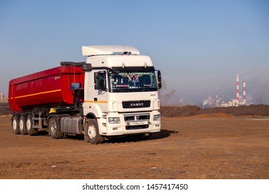 Russia Kemerovo 2019-04-09 red and white model Kamaz on field on background of the city landscape and factory pipes. Concept truck on Rally Dakar in desert. Scale model in sand
