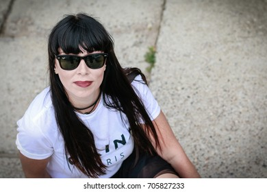 Russia, Kirov - August, 07, 2017: Portrait of woman in fashionable clothes with black hair and black glasses outdoor
