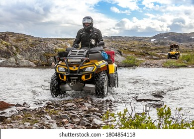 Russia, Kola Peninsula, June 20, 2013: A man crosses a river on an ATV BRP Can-Am Outlander. Art noise, selective focus, soft focus, motion blur.