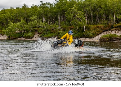 Russia, Kola Peninsula, June 2013: a man crosses the river on an ATV BRP Can-Am Outlander.