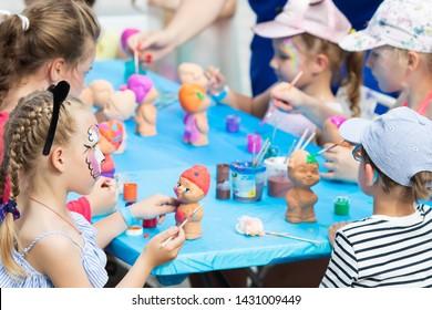 RUSSIA, KRASNODAR - JUNE 1 2019: Little girls painting ceramic funny gnome sculptures. Workshop for children at International children Day.