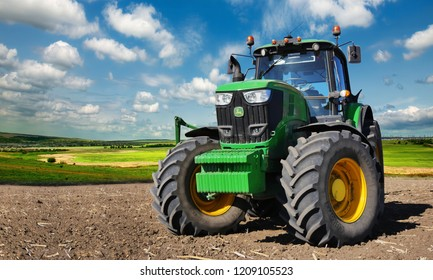 Russia, Krasnodar region, Kushevsky district.16.10.2018.   Modern, green tractor in the spring field work on the background of a beautiful rural landscape.